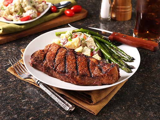 Steakhouse rubbed strip steak with potatoes and asparagas complete this steak recipe.