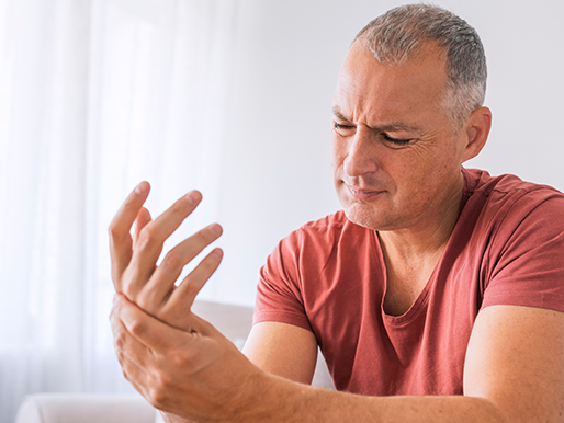 Man holding wrist with painful expression