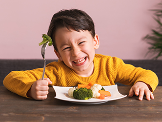 Kid smiling with fork full of food