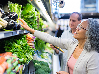 Older woman with grey hair choosing produce