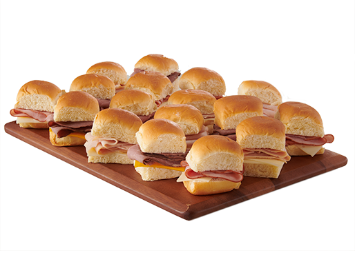 Slider sandwiches with lunch meats and cheese on a wooden serving board