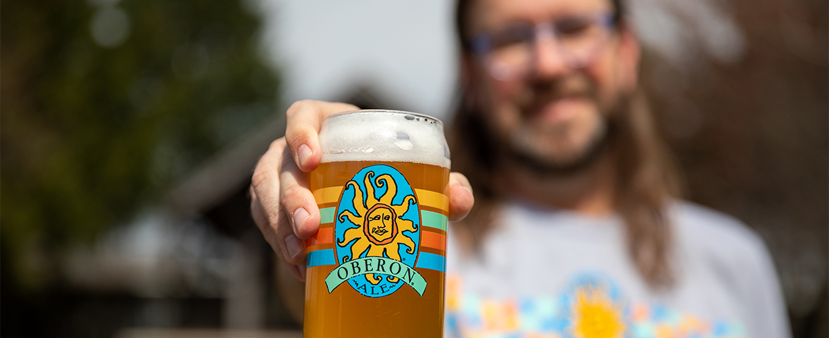 Smiling person offering a beer.