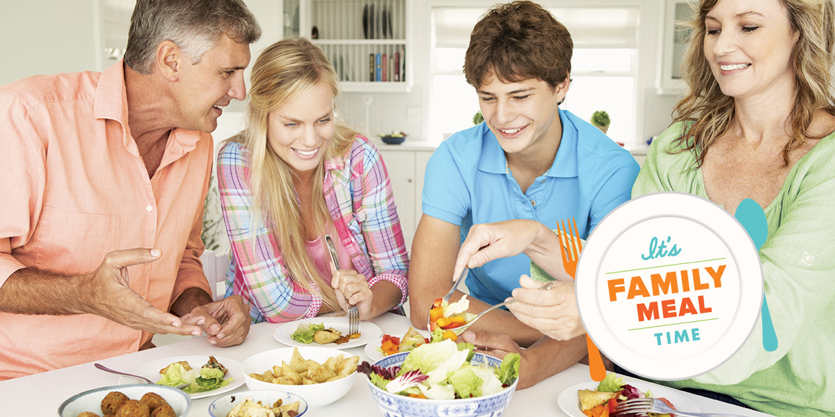 A happy family enjoying conversation and  a family meal together during Family Meals Month.