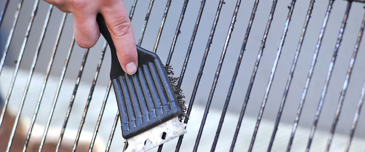 person scrubbing grill grate with brush