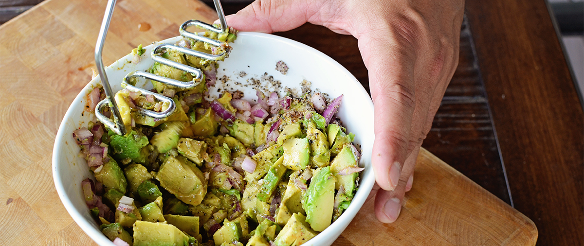 This guacamole recipe starts to take shape as the cook mashes the avacados and ingredients togther in this tasty and heathy recipe.